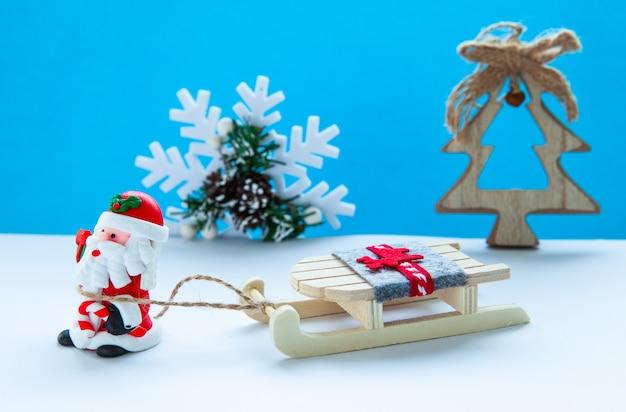 Koncepcja wakacji noworocznych. święty mikołaj z saniami na jasnoniebieskim tle