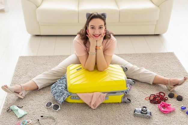 Koncepcja wakacji, podróży i podróży - młoda kobieta zbiera walizkę w domu w sypialni, dużo rzeczy, wakacje i żółtą walizkę.
