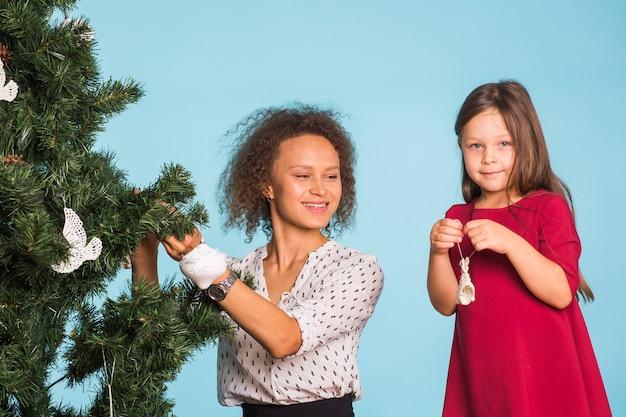 Koncepcja wakacji, rodziny i świąt - rasy mieszanej matka i córka dekorują choinkę