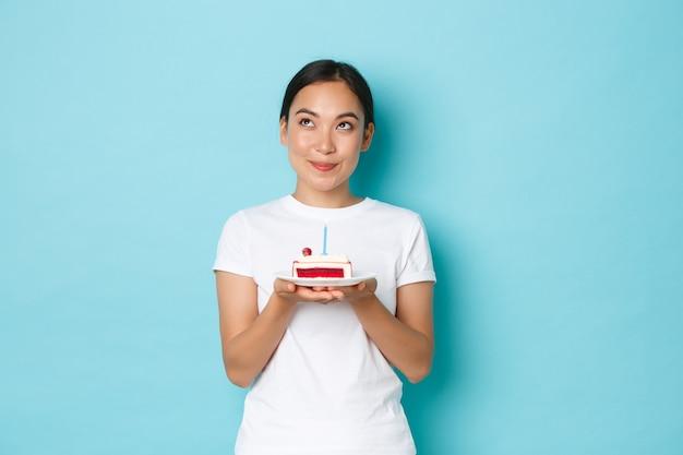 Koncepcja wakacji, stylu życia i uroczystości. portret marzycielskiej uśmiechniętej azjatki w białej koszulce, patrząc zamyślony, trzymając kawałek tortu urodzinowego, składając życzenie na zapalonej świecy.