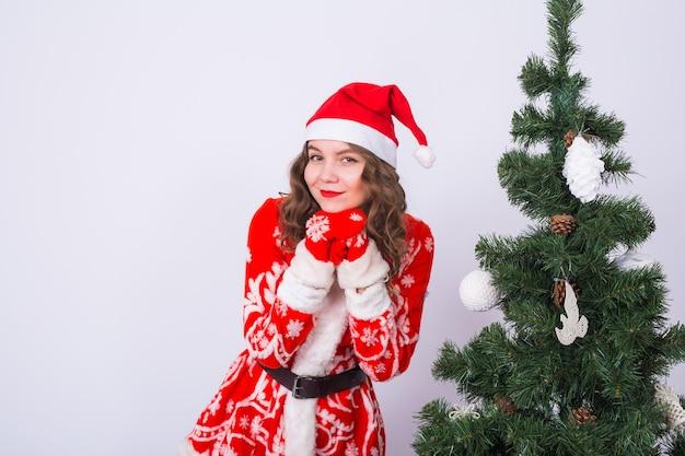 Koncepcja wakacji, świąt i zabawy - zabawna kobieta w stroju świętego mikołaja w pobliżu choinki na białej ścianie.