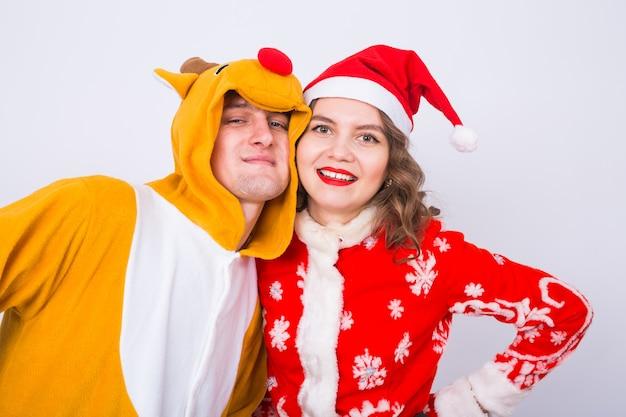 Koncepcja wakacji, świąt i zabawy - zabawna para w stroju jelenia i świętego mikołaja, przytulanie się na białej ścianie.