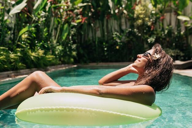 Koncepcja wakacji. urocza stylowa kobieta w okularach przeciwsłonecznych i kostiumie kąpielowym relaks w odkrytym basenie spa w słoneczny dzień