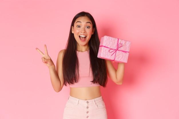 Koncepcja wakacji, uroczystości i stylu życia. uśmiechnięta azjatycka dziewczyna kawaii pokazująca zapakowany prezent i gest pokoju, lubi dawać prezenty, stojąc na różowym tle. skopiuj miejsce