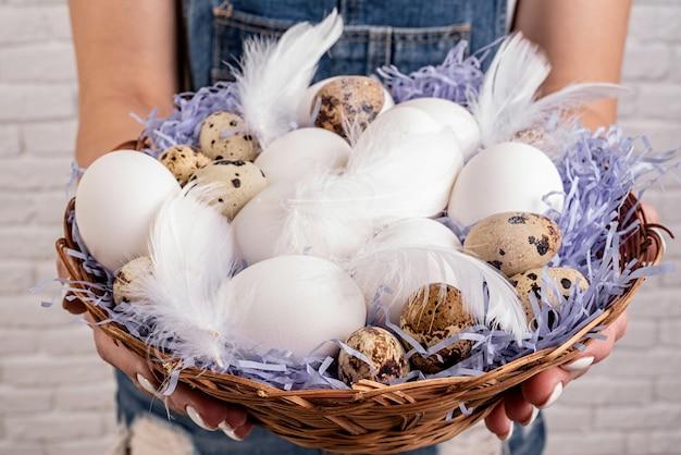 Koncepcja wakacji wielkanocnych. kobieta ręce trzymając duży kosz z jajami i piórami widok z przodu