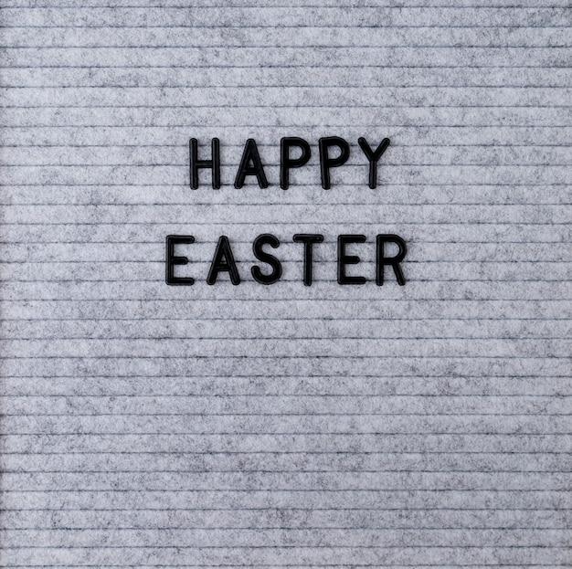 Koncepcja wakacji wielkanocnych. słowa wesołych świąt na szarej filcowej tablicy