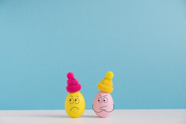 Koncepcja wakacji wielkanocnych z słodkie jajka z zabawnymi twarzami. różne emocje i uczucia. para w kłótni