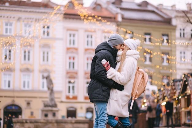 Koncepcja wakacji, zimy, bożego narodzenia i ludzi - szczęśliwa para w ciepłych ubraniach spacerująca po starym mieście