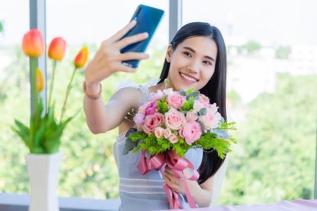 Koncepcja walentynek, selfie of happy uśmiechniętej azjatyckiej młodej kobiety siedzącej przy stole z jedzeniem z bukietem róż w restauracji