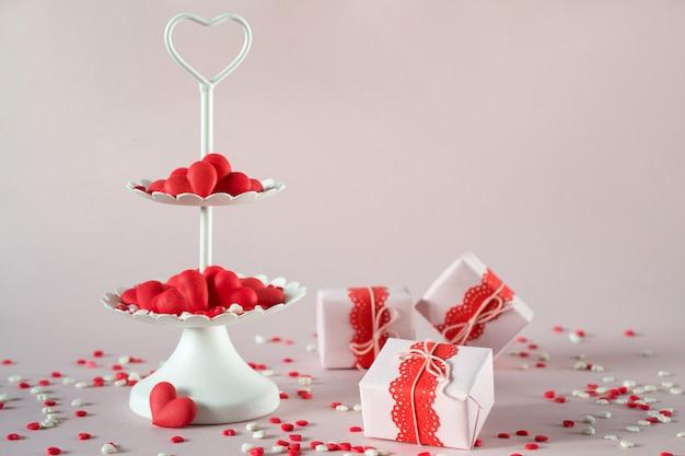 Koncepcja walentynki. biała dwupoziomowa taca pełna kolorowych cukierków posypuje serca cukierków cukrowych i pakuje prezenty walentynkowe