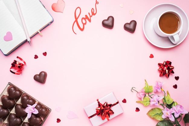 Koncepcja walentynki. czekoladowe cukierki i kawa, serca na różowym tle. płaskie miejsce leżał kopia. kartkę z życzeniami i prezent.
