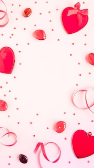 Koncepcja walentynki czerwone serca i wstążki na różowym tle