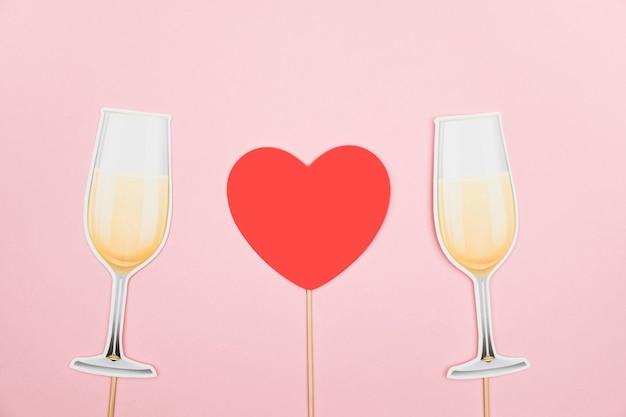 Koncepcja walentynki czerwone serce i kieliszki do szampana papierowe rekwizyty na różowym tle