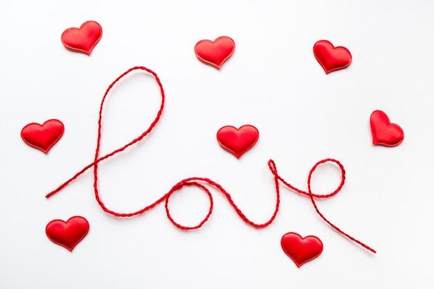 Koncepcja walentynki czerwone serce i słowo miłość wykonane z wełnianej liny na białym tle