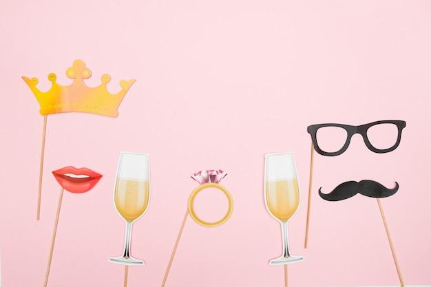 Koncepcja walentynki czerwone serce, kieliszek do szampana, wąsy i usta papierowe rekwizyty na różowym tle