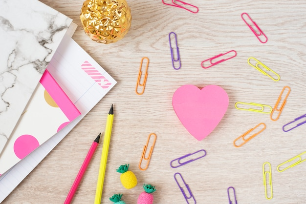 Koncepcja walentynki. freelance modne miejsce do pracy kobiecości w płasko ułożonym stylu z różowymi papierowymi sercami, marmurowym folderem, notatnikiem, różowymi neonowymi papeteriami na szarym drewnianym