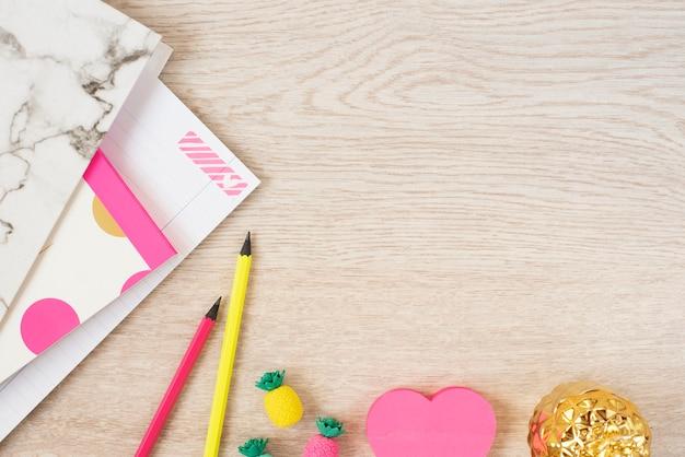 Koncepcja walentynki. freelance modne miejsce do pracy z kobiecością w płaskiej stylistyce z sercami, marmurową teczką, notatnikiem, różowymi neonowymi materiałami na szarym drewnie