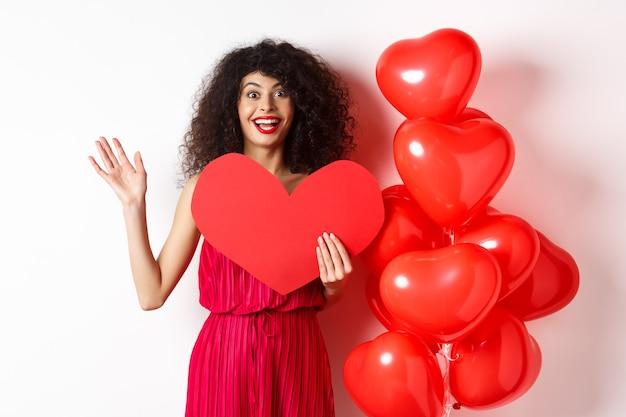 Koncepcja walentynki i miłość. wesoła młoda kobieta w eleganckiej czerwonej sukience, stojąca w pobliżu romantycznych balonów i trzymająca duże czerwone serce, machająca ręką, żeby się przywitać, czekając na randkę.