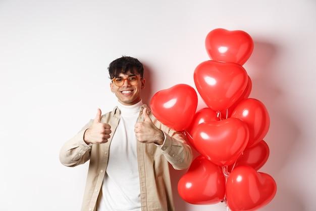 Koncepcja walentynki i romans. stylowy, nowoczesny mężczyzna w okularach przeciwsłonecznych pokazujący kciuki do góry, stojąc w pobliżu balonów w kształcie serca, mówiąc tak, ciesz się randką z kochankiem.