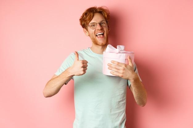 Koncepcja walentynki i romans. wesoły młody mężczyzna trzyma pudełko z prezentem i pokazuje kciuk w górę, dziękując za prezent, stojąc na różowym tle.