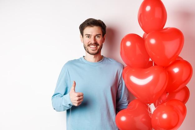 Koncepcja walentynki i samotności. szczęśliwy młody człowiek pokazując kciuki do góry jako stojący z balonem z czerwonym sercem, przynieś romantyczny prezent na randkę, stojąc na białym