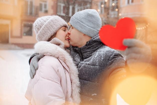 Koncepcja walentynki, kochająca para całować i przytulać w śnieżnym parku zimą. młody mężczyzna trzyma czerwone papierowe serce, świętując dzień wszystkich kochanków ze swoją dziewczyną. para czuje się ciepło razem.
