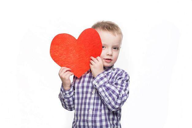 Koncepcja walentynki - mały chłopiec z czerwonym sercem. pojedynczo na białym tle studio