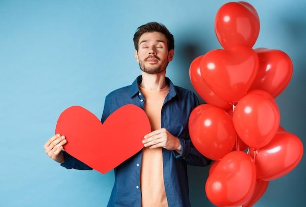 Koncepcja walentynki. mężczyzna marzy o prawdziwej miłości, trzymając wycinek z czerwonego serca i stojący w pobliżu romantycznych balonów, niebieskie tło.