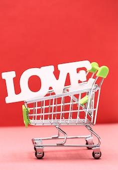 Koncepcja walentynki od słowa miłość w wózku na zakupy na czerwonym tle papieru