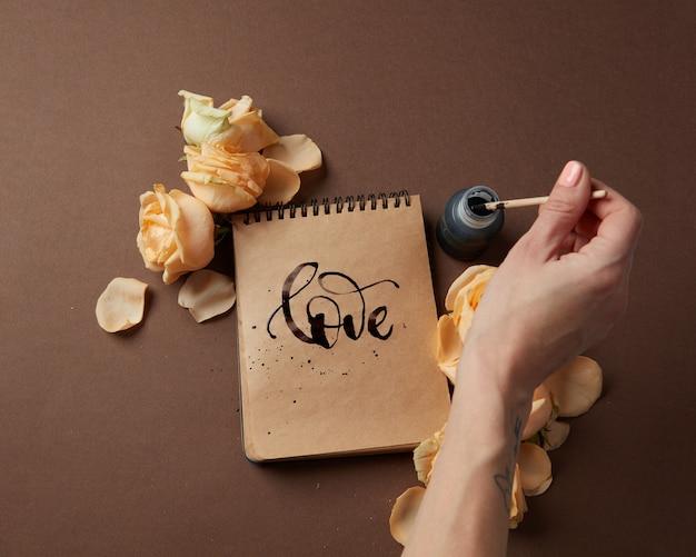 Koncepcja walentynki. pamiętnik lub notatnik ze słowem miłość napisanym przez kobietę. kobieca ręka pisze w dzienniku z brązowymi stronami nad brązowym stołem.