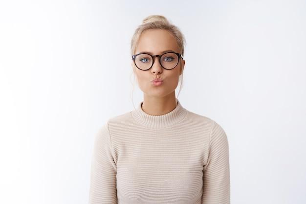 Koncepcja walentynki, piękno i styl życia. zabawna i zalotna, atrakcyjna młoda europejska kobieta w okularach składa usta, wysyłając pocałunek w powietrzu, będąc romantyczną, pokazując współczucie mwah nad białą ścianą