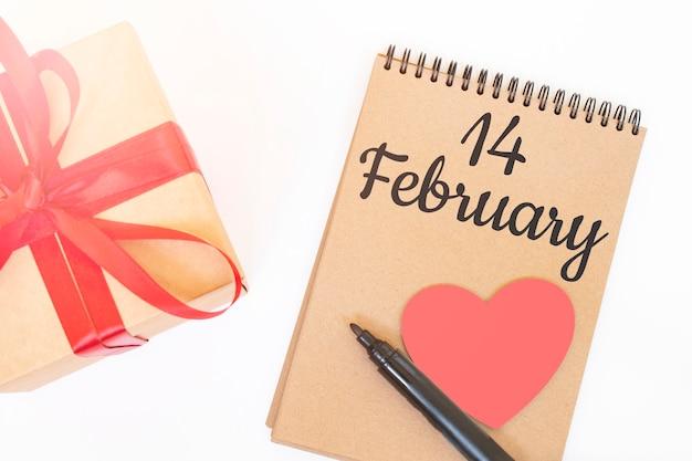 Koncepcja walentynki. pudełko upominkowe creaft z czerwoną wstążką, różowym drewnianym sercem, czarnym markerem i notatnikiem w kolorze rzemieślniczym z napisem 14 lutego