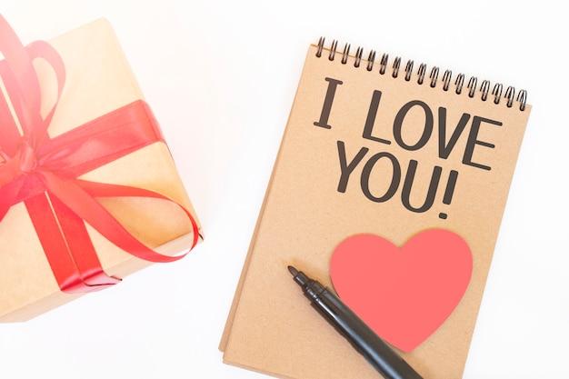 Koncepcja walentynki. pudełko upominkowe creaft z czerwoną wstążką, różowym drewnianym sercem, czarnym markerem i notatnikiem w kolorze rzemieślniczym z napisem i love you
