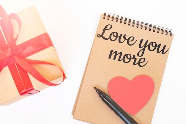 Koncepcja walentynki. pudełko upominkowe creaft z czerwoną wstążką, różowym drewnianym sercem, czarnym markerem i notatnikiem w kolorze rzemieślniczym z napisem love you more