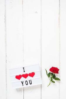Koncepcja walentynki świeży czerwony kwiat róży i tekst kocham cię na lightbox na białym tle drewniane