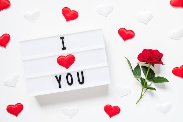 Koncepcja walentynki świeży czerwony kwiat róży, serca i tekst kocham cię na lightbox na białym tle