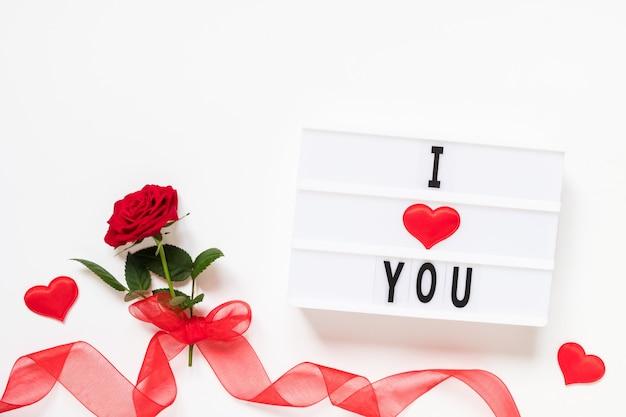 Koncepcja walentynki świeży czerwony kwiat róży z wstążką i tekstem kocham cię na lightbox na białym tle