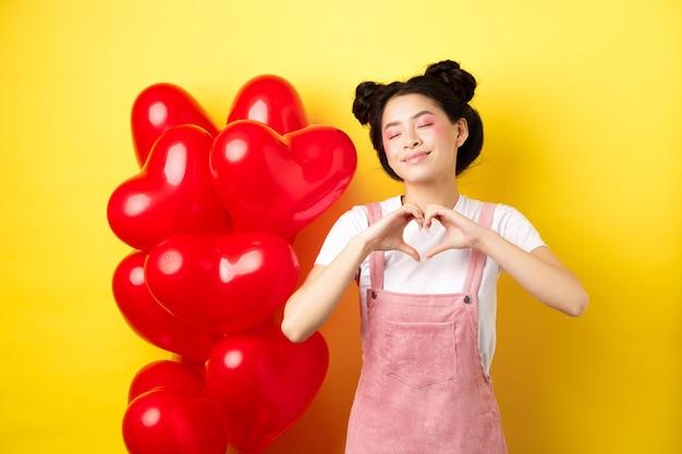 Koncepcja walentynki. urocza azjatycka dziewczyna marzy o romansie, zamyka oczy i pokazuje gest serca, uśmiechnięta szczęśliwa, stojąca w pobliżu czerwonych romantycznych balonów, żółte tło.