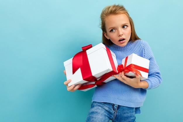 Koncepcja walentynki. urocza dziewczyna ledwo trzyma dwa prezenty na jasnoniebieskim tle