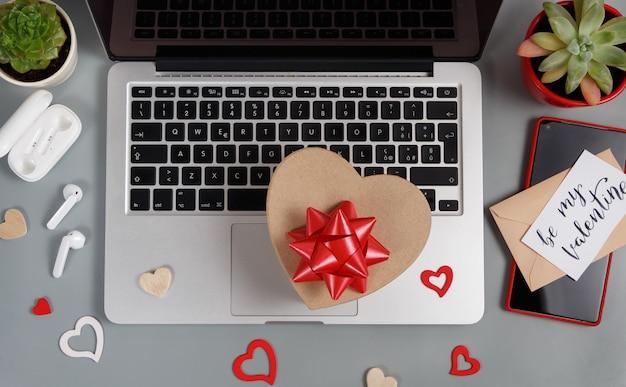 Koncepcja walentynki z nowoczesnymi gadżetami, pudełkiem prezentowym i widokiem z góry karty be my valentine na szarym stole