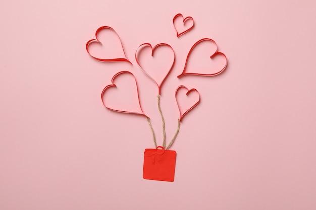 Koncepcja walentynki z ozdobnymi sercami i pudełko na różowym tle