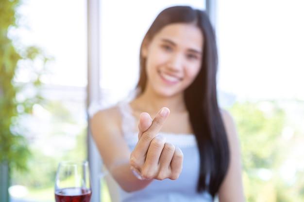 Koncepcja walentynkowa, kształt serca lub mini serce wykonane ręcznie z szczęśliwej azjatyckiej młodej kobiety siedzącej przy stole jedzenie z kieliszkami do wina i bukietem czerwonych i różowych róż w tle restauracji