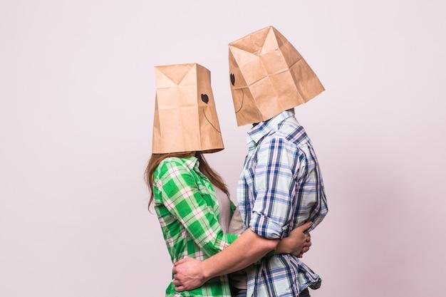 Koncepcja walentynkowa - młoda miłość para z torbami nad głowami na białym tle