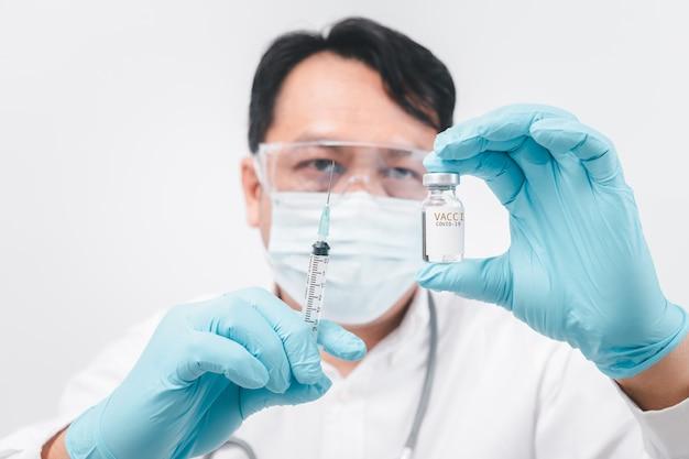 Koncepcja walki z wirusem covid-19 corona virus, młody lekarz lub naukowiec w koszuli, trzymający szczepionki covid-19. koncepcja medyczna i naukowa