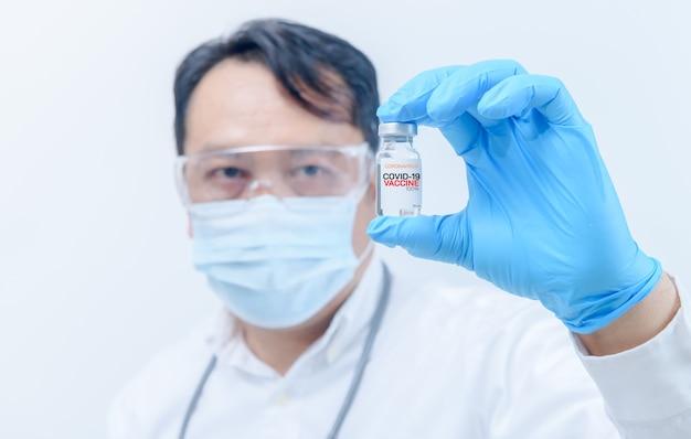 Koncepcja walki z wirusem covid-19 koronawirusa, młody lekarz lub naukowiec w koszuli ze szczepionkami przeciwko covid-19. koncepcja medycyny i nauki