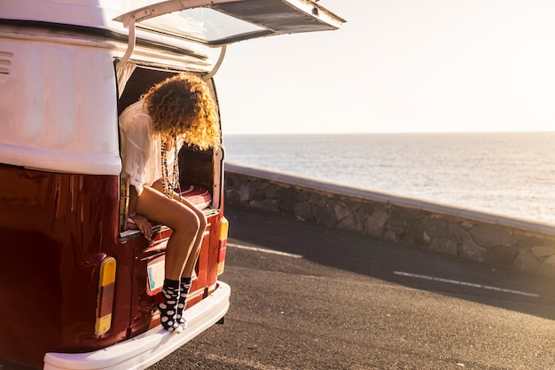 Koncepcja wanderlust i vanilife z młodym podróżnikiem rasy kaukaskiej kobieta siedzi z rocznika retro legenday van gotowy do podróży po świecie. zachód słońca i ocean przed nią zaparkowany tuż nad morzem?