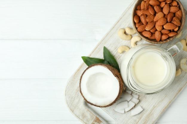 Koncepcja wegańskiego mleka na białym drewnianym tle, widok z góry