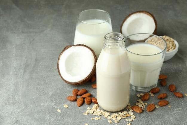 Koncepcja wegańskiego mleka na szarym tle z teksturą
