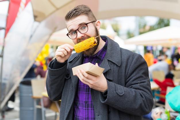 Koncepcja wegetariańska i posiłek - przystojny mężczyzna jedzenie kukurydzy ulicznej na festiwalu fast food