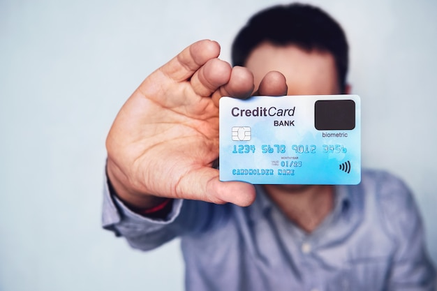 Koncepcja weryfikacji biometrycznej na karcie kredytowej. posiadacz karty pokazujący kartę płatniczą z czujnikiem na palec. dokonaj zakupu za pomocą technologii skanera linii papilarnych. młody człowiek z kartą kredytową nowej generacji.